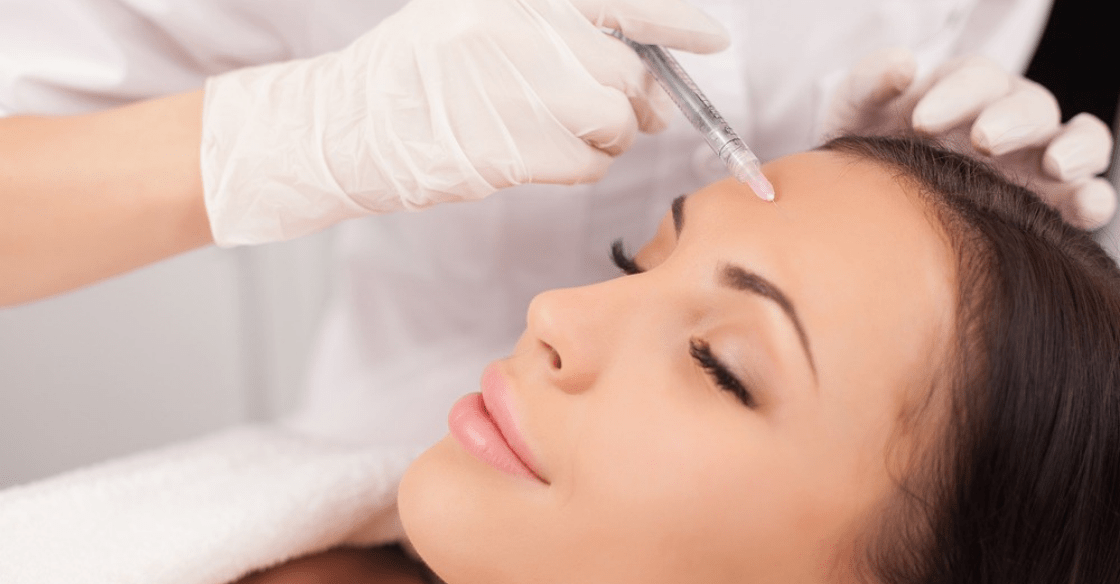 A practitioner is injecting a women's forehead with Botox