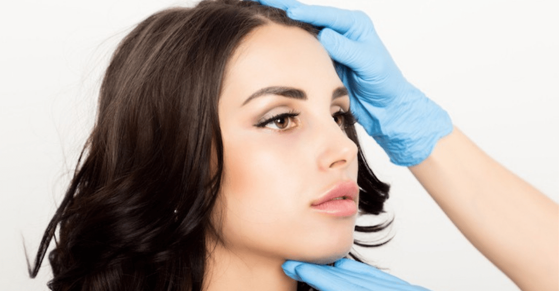 Brown haired woman getting her facial features examined for Botox.